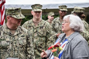 GARDINER, Wash. (Nov. 11, 2016) Mrs. Joan Shields-Bennett, widow of Construction Mechanic 3rd Class Marvin Glenn Shields, describes the tributes left on the grave of her late husband to Lt. j.g. David Fickey, a Titusville, Florida, native and assistant public works officer at Naval Station Everett, after a Veterans Day ceremony hosted by Naval Facilities Engineering Command Northwest at Gardiner Cemetery. The ceremony paid tribute to the only Seabee Medal of Honor recipient and Vietnam veteran, Shields, who was posthumously awarded the nation's highest military award for his actions taken and giving his life to save comrades while under enemy attack. (U.S. Navy photo by Petty Officer 1st Class Cory Asato/Released)