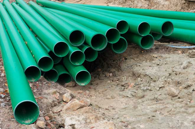 Stack of Green PVC Pipes