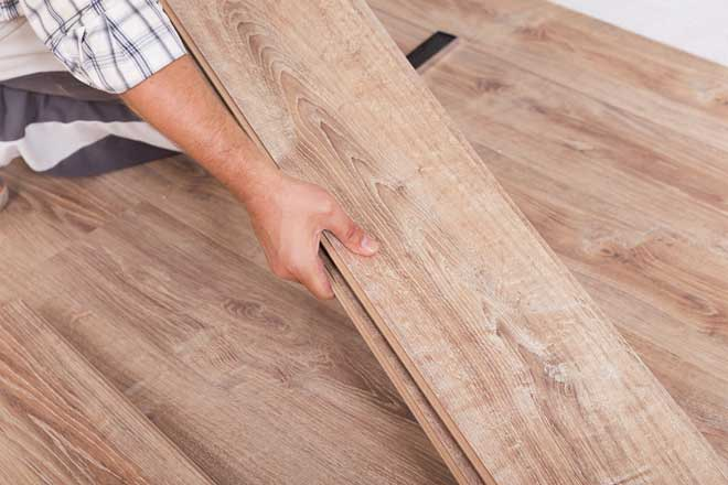 Carpenter Installing New Laminate Wood Flooring