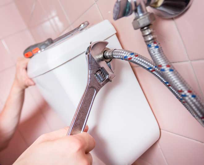 Plumber Repairing Toilet with Wrench