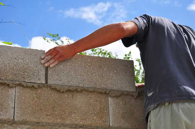 Man Assembling Cinder Block Wall