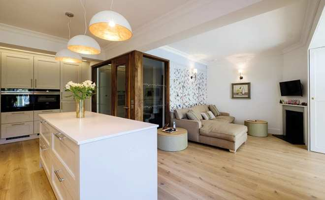 The Kitchens International kitchen was hand-painted on site and complements the engineered oak floorboards. The pendants were sourced by Bryce McKenzie Design and Decoration