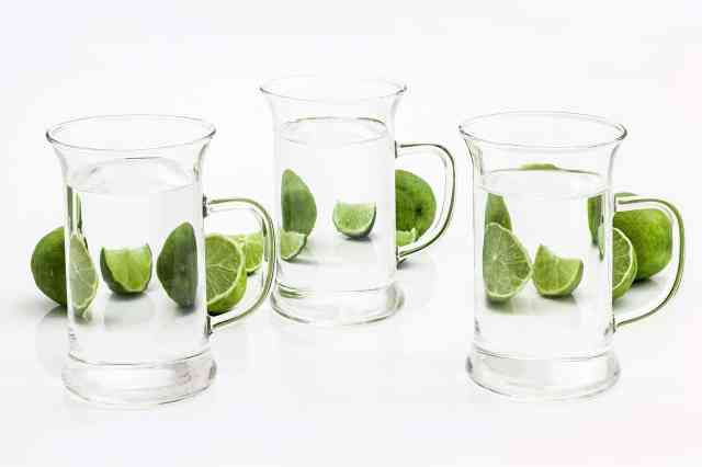 benefits of lime water. 3 glasses of water shown with slices of lime around them.
