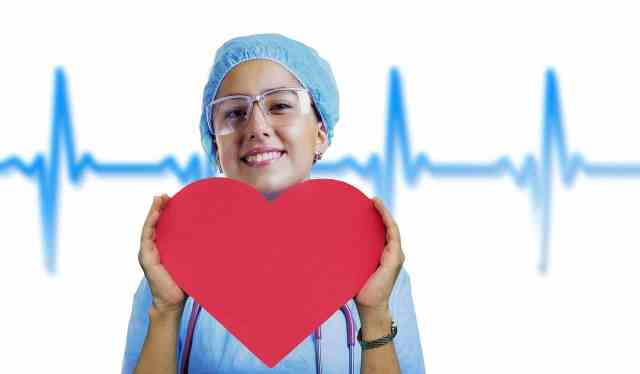 medical person holding a paper heart in her hand. benefits of lime water