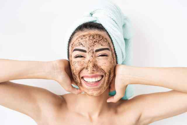 Best Sensitive Skin Care Tips-Young smiling woman applying coffee scrub mask on face - Happy girl having skin care spa day at home - Healthy alternative natural exfoliation treatment and people lifestyle concept
