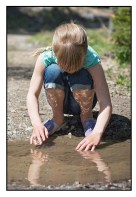 Girls is touching the water in a puddle.