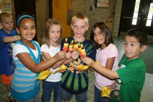 5 kids holding shared fruit sticks