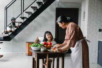 cheerful little asian girl sitting at table while grandmother serving lunch with fresh veggies