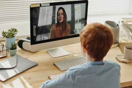 photo of boy video calling with a woman
