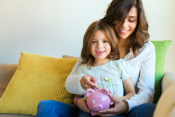 brunette mother sitting on a couch with a young girl on her lap putting money into a piggy bank