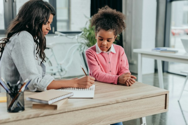 black mother and daughter sitting at kitchen table doing homeschool