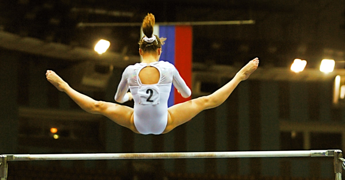 Olympic homeschoolers young woman flying over the uneven bars