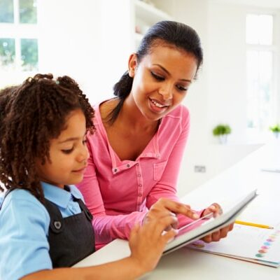 qualifications to homeschool my child black mother and child sitting at kitchen table with an ipad and workbook on table