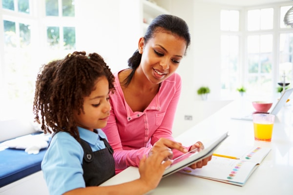 qualifications to homeschool my child: black mother and elementary age child sitting at kitchen table with an ipad and workbook on table