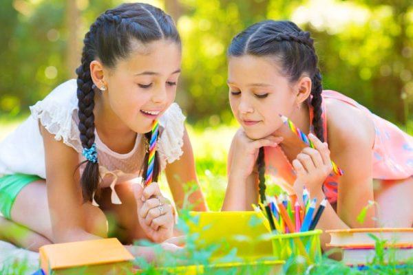 two tween girls in braids sitting in yard and working on Homeschool Unit Studies Ideas