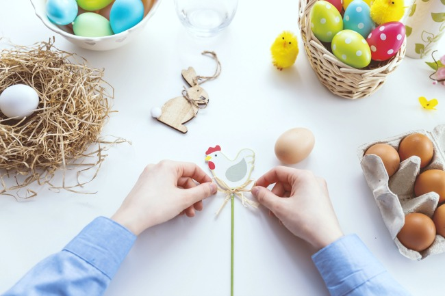ideas for Easter eggs on a table with different colored eggs and hands tying a ribbon on a chicken decoration
