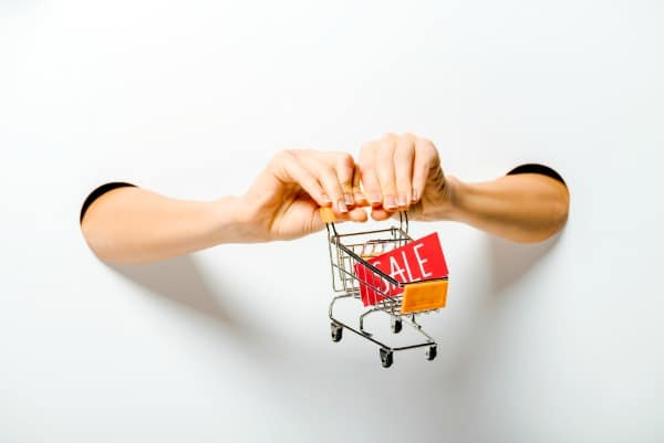 Best Amazon Prime Day Tips and Tricks hands pushing a mini shopping cart with amazon sale sign in it