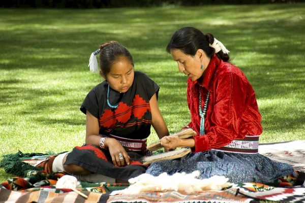 Native American Heritage Month Lessons + Make a Totem Pole Craft! an indigenous grandmother and granddaughter sitting on the ground working on a craft