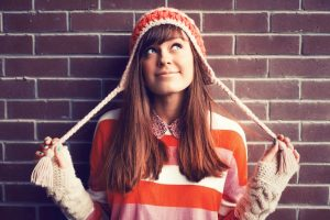Unschooling smiling High School caucasian high school female in a knitted hat leaning against a brick wall and looking up