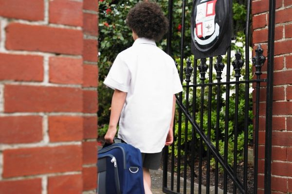 Homeschool vs Private School back of child in school uniform walking into a private school