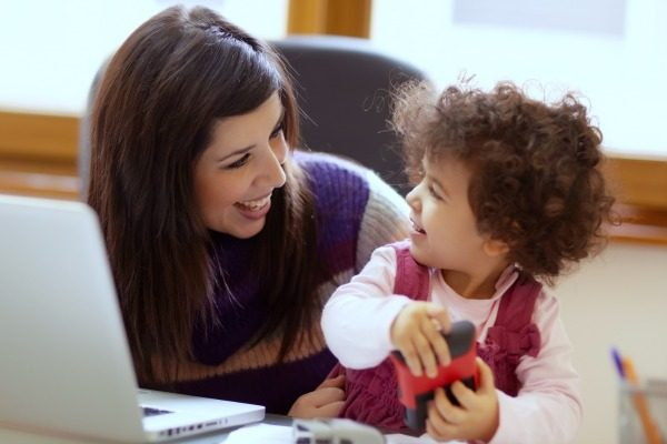 young mom with a laptop on a table and smiling at a toddler sitting next to her