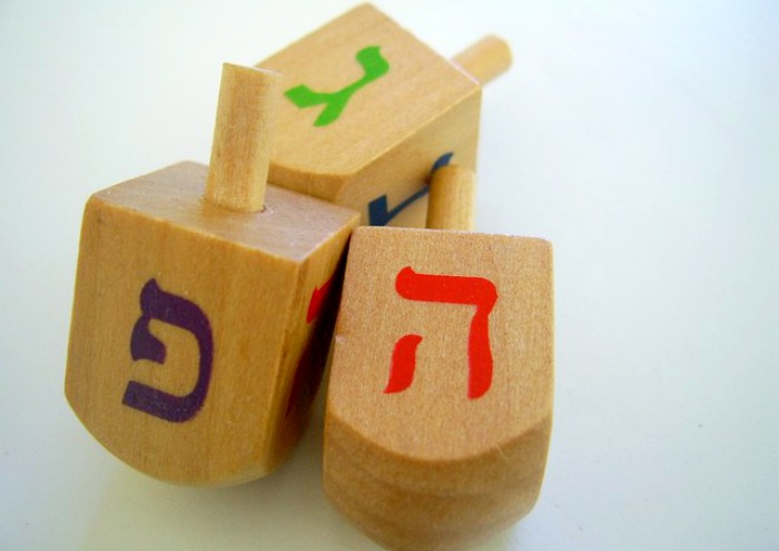3 wooden Hanukkah dreidel toys on a white table