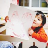 how to homeschool kindergarten little girl showing a crayon drawing
