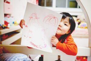 how to homeschool kindergarten little girl showing a crayon drawing