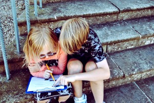 a boy and a girl sitting on a cement step outside and reading a book together