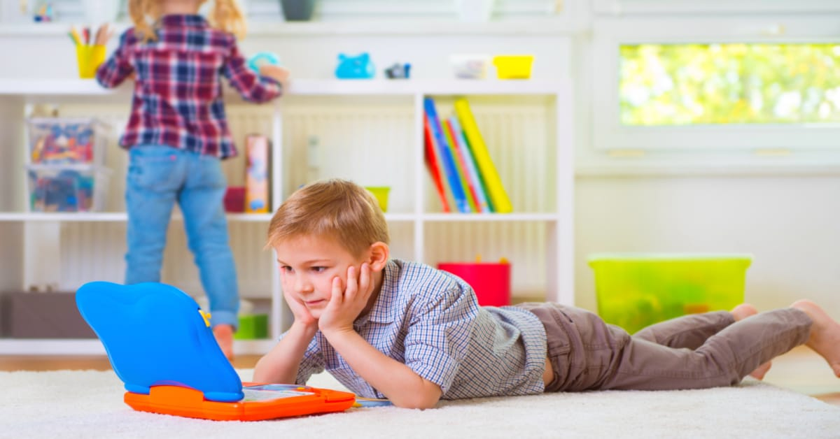 How does homeschooling work young homeschooled boy laying on floor and looking at a laptop
