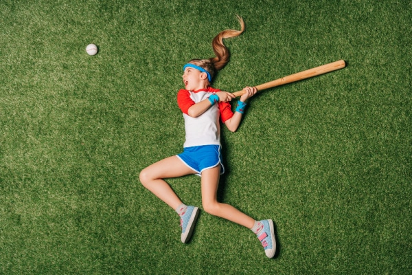 Home School Sports girl laying on the grass and swinging at a base ball with a bat