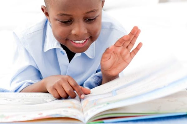 Kindness acts for kids with young black boy reading a kindness book