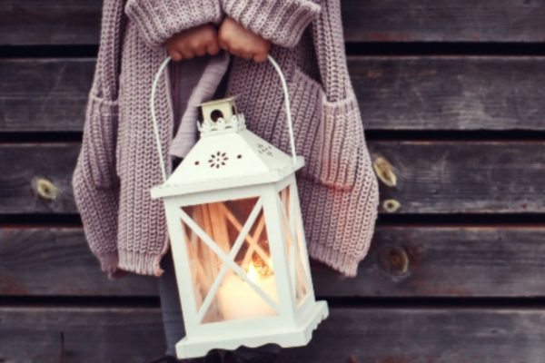 4 Important Homeschooling Requirements You Must Know Before Starting woman's hands holding a lantern with a candle in it and leaning against side of a barn