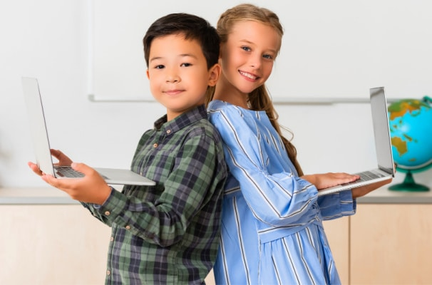 Home school versus virtual school elementary age home learners boy and girl holding laptops