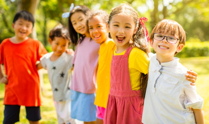 Homeschool Social Groups with a diverse social group of kids linking arms and playing outside