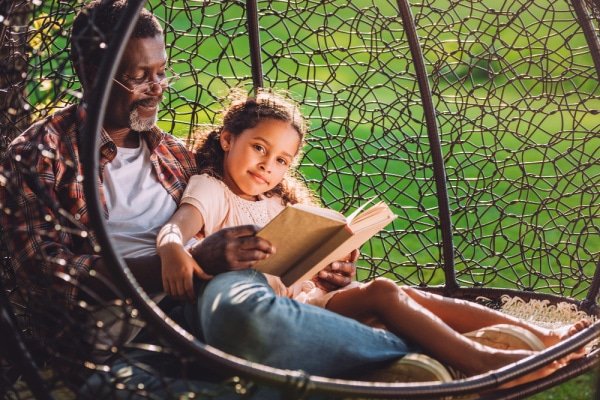 african american grandpa sitting on a swing with an black elementary age girl and reading a book together for Homeschool Without Internet
