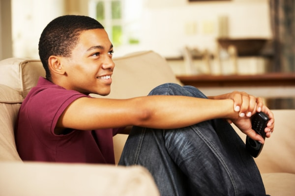 Homeschooling vs Unschooling black smiling male teen sitting on couch with tv remote in hand