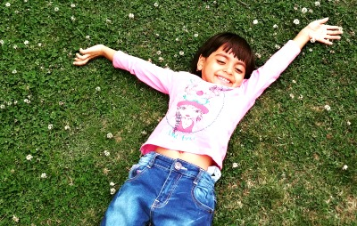 What Does Deschooling Mean? little girl lying in the grass laughing with arms over head