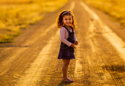 What Is Unschooling Homeschooling? girl looking back over should and smiling while walking on dirt road