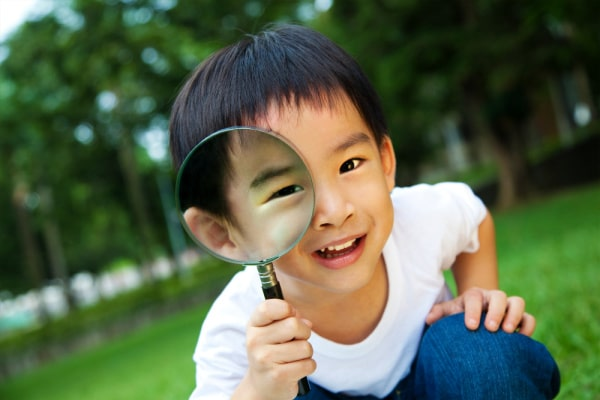 What Is Unschooling cute asian boy looking through a magnifying glass outside