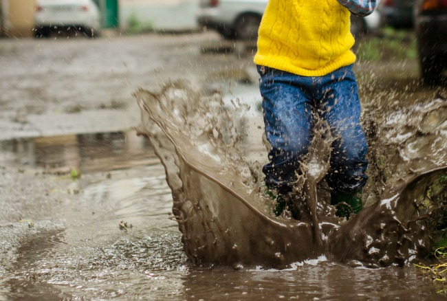 What Is Unschooling? Ultimate Guide to Everything Unschool child stomping in a mud puddle