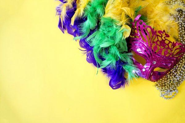 Mardi Gras mask with purple, yellow, and green feathers on a yellow table