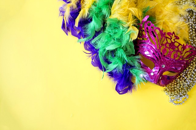 What Mardi Gras means: Mardi Gras mask with purple, yellow, and green feathers on a yellow table