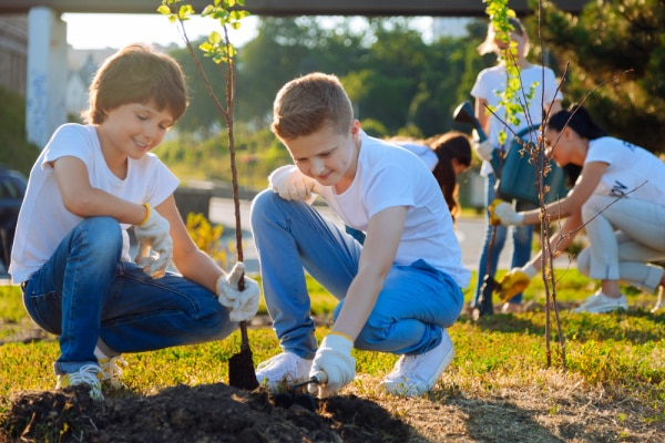 Arbor Day Activities for Kids two tween boys planting a tree seedling with other kids planting int the background