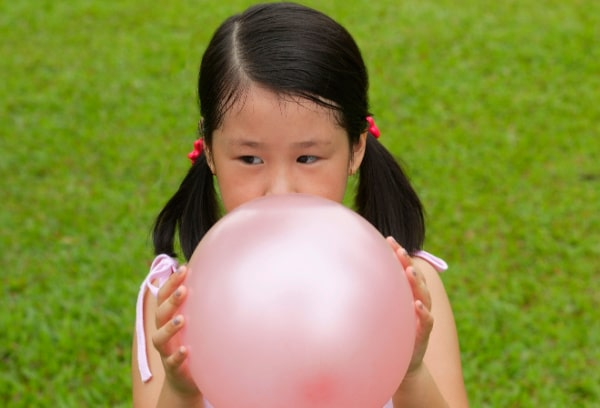 Autism awareness for kids young girl with dark ponytails blowing up a balloons on green grass