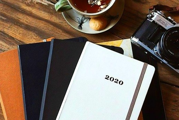 stacks of yearbooks with 2020 on top and a cup of tea and a camera all sitting on a table