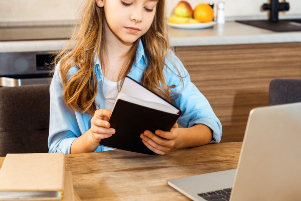 caucasian preteen girl sitting at kitchen table working on home school programs with laptop and books