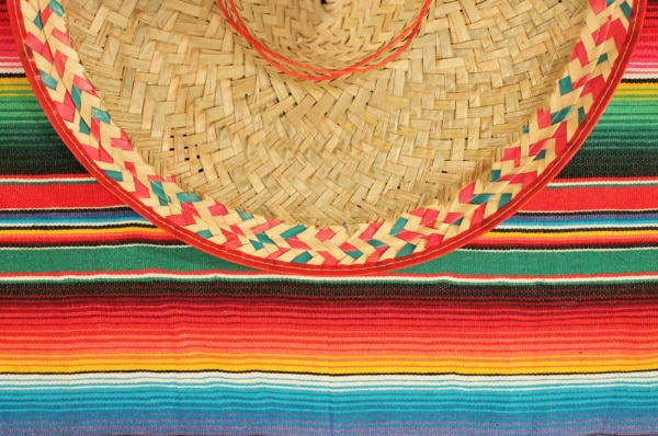 Cinco De Mayo History For Kids with sombrero sitting on brightly colored blanket