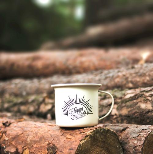 happy camper mug sitting on logs outside