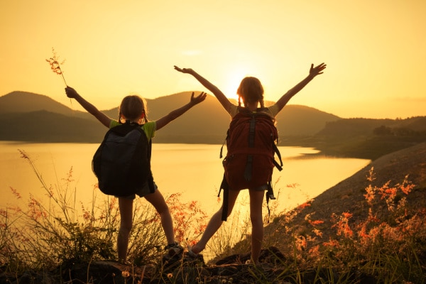 How To Hike With Kids two tween girls with hiking backpacks looking at water with arms up